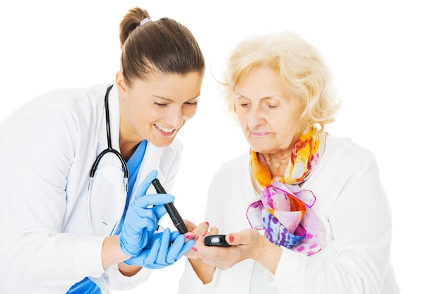 Молодая женщина-врач, исследующая уровень сахара в крови старшей женщины, изолированные на белом фоне