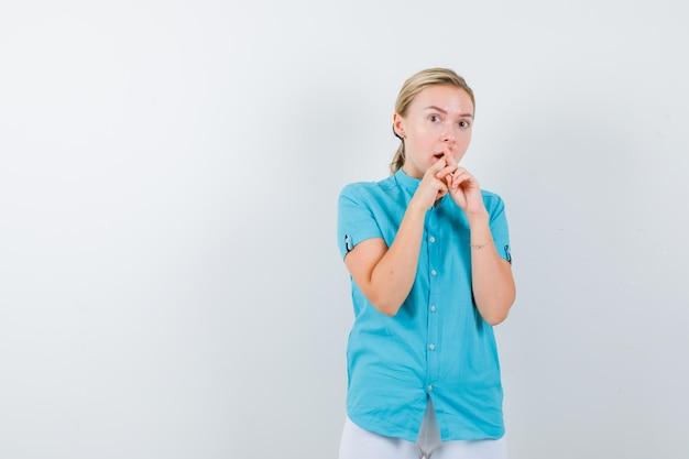医療制服を着て口の近くで交差した指を保持している若い女性医師