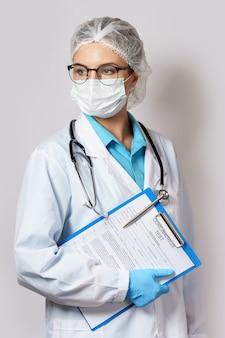 コロナウイルス検査フォームが入ったフォルダーを持つ若い女性医師