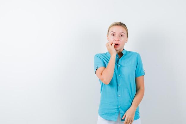 젊은 여성 의사 의료 유니폼, 마스크에 뺨에 손을 잡고 의아해 찾고