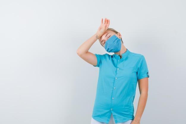 Молодая женщина-врач держит руку на лбу в медицинской форме, маске и выглядит усталой