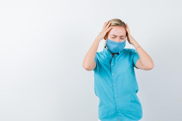 젊은 여성 의사 유니폼을 입고 머리에 손을 잡고 지쳐보고