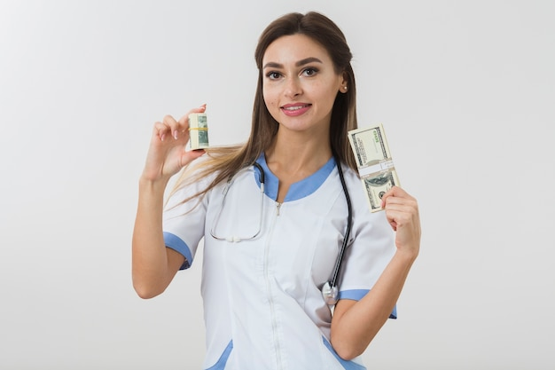 Young female doctor holding money
