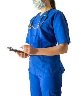 青い医療制服とノートにメモを取るマスクの若い女性医師