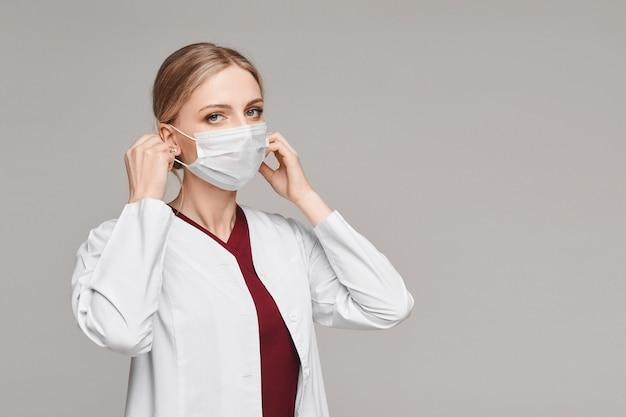Молодая женщина-врач в медицинском халате, надевая защитное покрытие лица, изолирована на белом