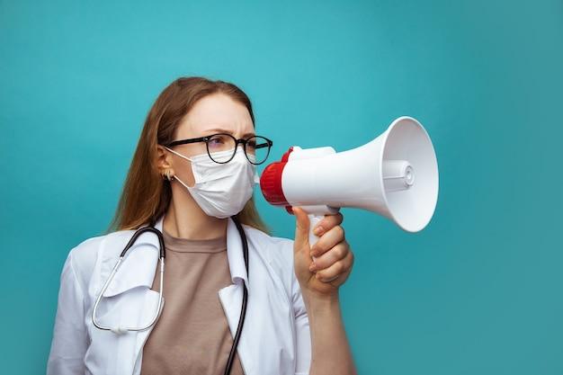 青でメガホンに叫んでいるフェイスマスクの若い女性医師。