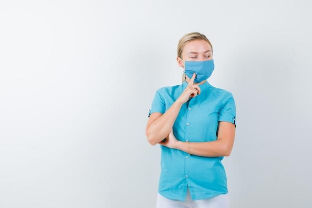 의료 제복을 입은 젊은 여성 의사, 생각에 서있는 마스크