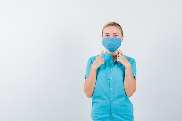 制服を着た若い女性医師が自分を指差して自信を持って見える
