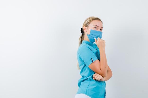 思考ポーズと自信を持って見える制服を着た若い女性医師