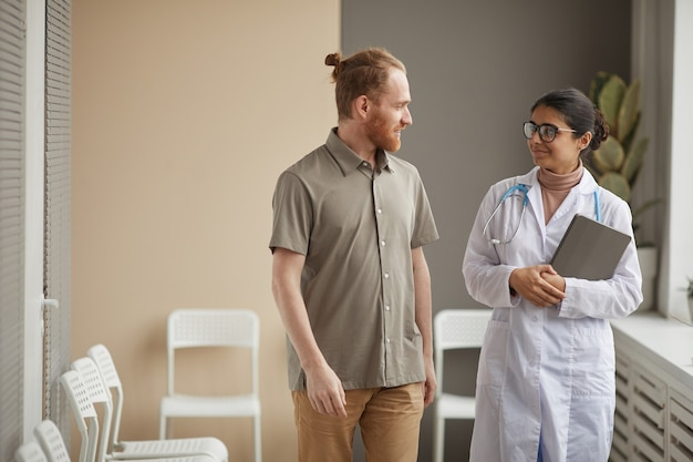 Молодая женщина-врач в белом халате разговаривает с пациентом-мужчиной, пока они идут по коридору в больнице