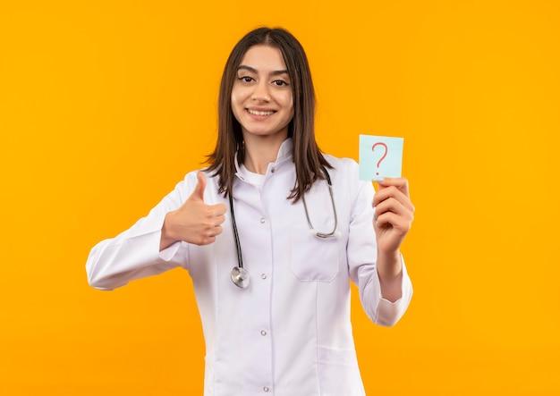 Молодая женщина-врач в белом халате со стетоскопом на шее держит бумагу для напоминания с вопросительным знаком, улыбаясь, глядя вперед, показывая пальцы вверх, стоя над оранжевой стеной