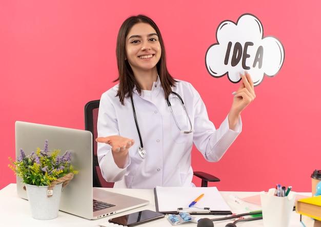 연설 거품 기호 아이디어를 들고 그녀의 목에 청진기와 흰색 코트에 젊은 여성 의사는 유쾌하게 분홍색 벽에 노트북과 테이블에 앉아 웃고