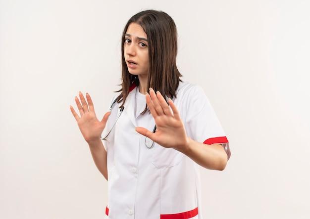 Молодая женщина-врач в белом халате со стетоскопом на шее делает защитный жест, протягивая руки, говоря, чтобы не подходить ближе, стоя над белой стеной