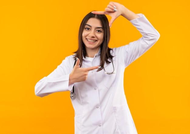 오렌지 벽 위에 서 웃고이 프레임을 통해 전면을보고 손가락으로 프레임을 만드는 그녀의 목 주위에 청진기와 흰색 코트에 젊은 여성 의사