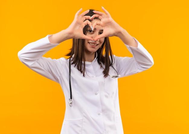 首に聴診器を持った白衣を着た若い女性医師が、オレンジ色の壁の上に立っている顔に笑顔で正面を向いている指でハートジェスチャーをしている