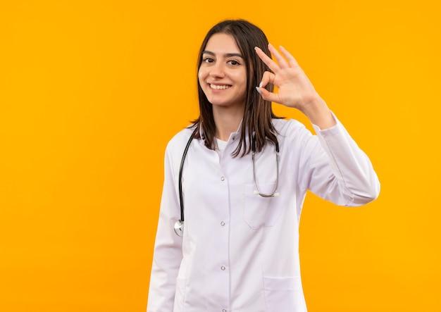 Молодая женщина-врач в белом халате со стетоскопом на шее делает знак ок с пальцами, улыбаясь, стоя над оранжевой стеной