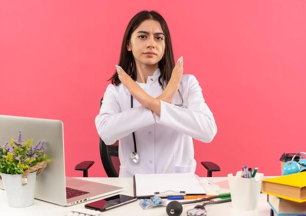 Молодая женщина-врач в белом халате со стетоскопом на шее делает знак остановки с серьезным лицом, скрещивающим руки, сидя за столом с ноутбуком над розовой стеной