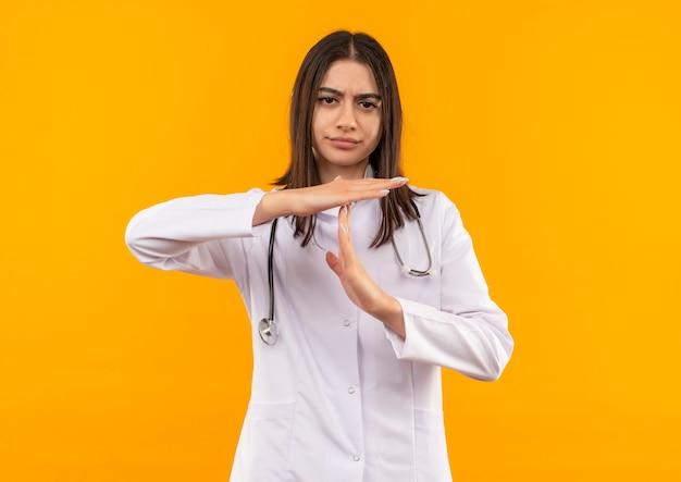 Молодая женщина-врач в белом халате со стетоскопом на шее делает жест тайм-аута с руками, смотрящими вперед, с нахмуренным лицом, стоящим над оранжевой стеной