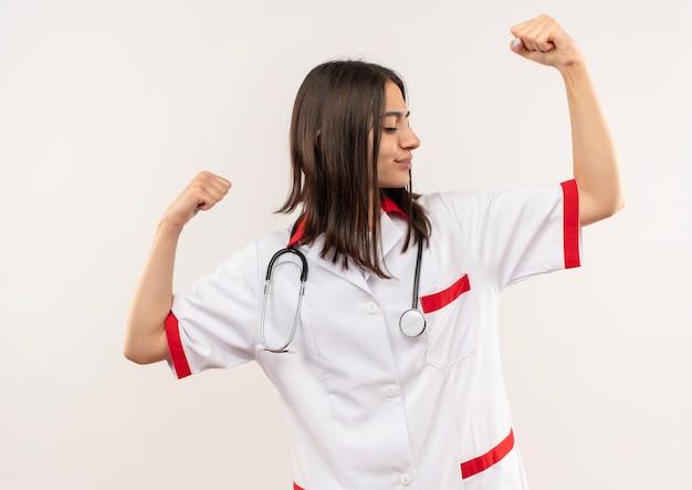 彼女の首の周りに聴診器を持った白いコートを着た若い女性医師が上腕二頭筋を示す手を上げ、白い壁の上に立っている勝者の概念
