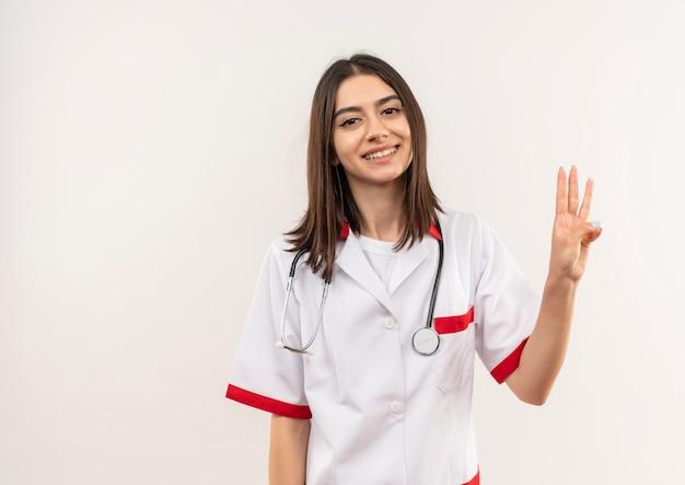 그녀의 목에 청진기와 흰색 코트에 젊은 여성 의사가 보여주는 손가락 세 번째는 흰 벽 위에 서 웃고 가리키는