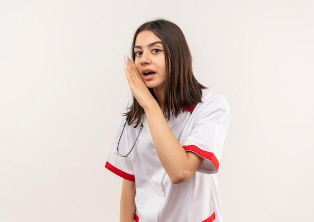 Молодая женщина-врач в белом халате со стетоскопом на шее рассказывает секрет рукой возле рта, стоящей над белой стеной