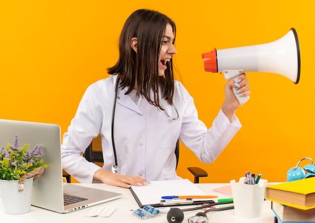 오렌지 벽 위에 노트북 및 문서와 함께 테이블에 앉아 공격적인 표정으로 확성기로 외치는 청진기와 흰색 코트에 젊은 여성 의사