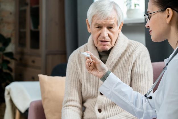 Молодая женщина-врач в белом халате, глядя на термометр после измерения температуры тела больного старшего мужчины, сидящего на диване в гостиной
