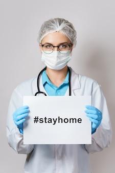 Молодая женщина-врач держит бумагу с хэштегом #stayhome