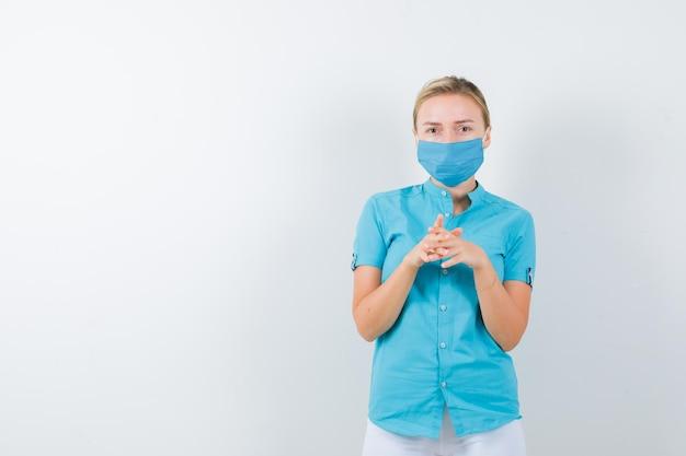Молодая женщина-врач держит сложенными руками возле груди в медицинской форме