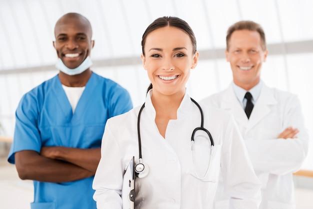 彼女のチームを率いる若い女性医師。彼女の同僚がバックグラウンドで彼女の後ろに立っている間クリップボードを保持し、笑顔の美しい女性医師