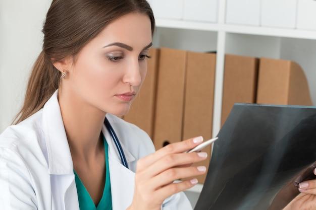 Молодая женщина-врач, глядя на рентгеновское изображение легких
