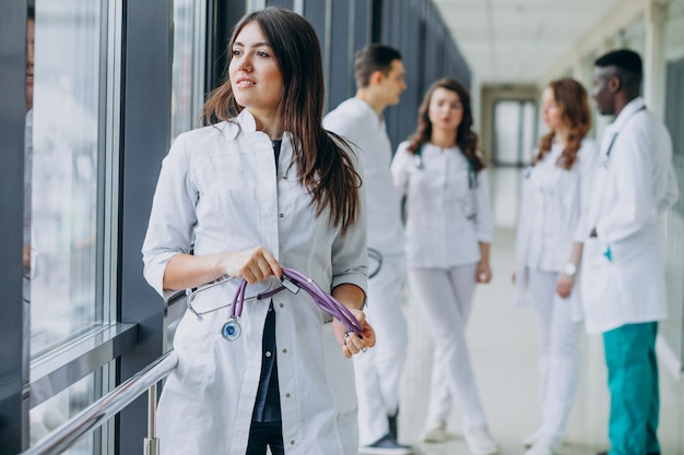 Молодая женщина-врач смотрит в окно из коридора больницы