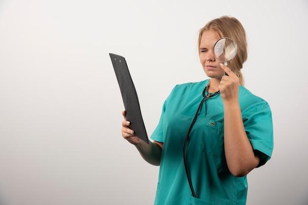 Giovane medico femminile che osserva tramite la lente di ingrandimento negli appunti.