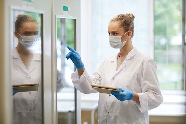 Young female doctor in mask and in white coat using digital tablet at work she pointing at fridge while working at the lab