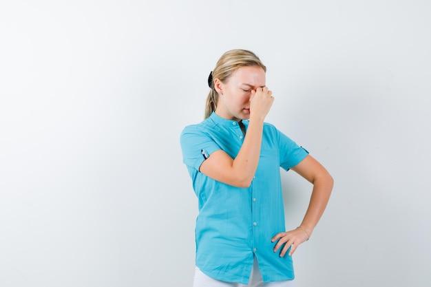 Молодая женщина-врач массирует переносицу в медицинской форме, маске и выглядит усталой