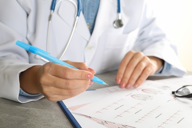 Young female doctor in medical gown checking electrocardiogram results