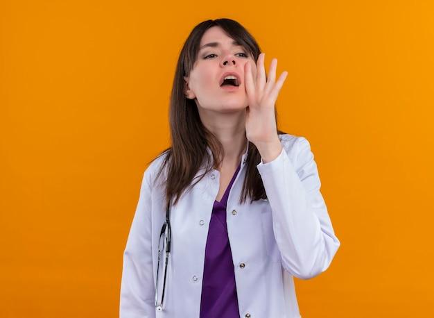 Il giovane medico femminile in abito medico con lo stetoscopio chiama qualcuno sulla parete arancione isolata