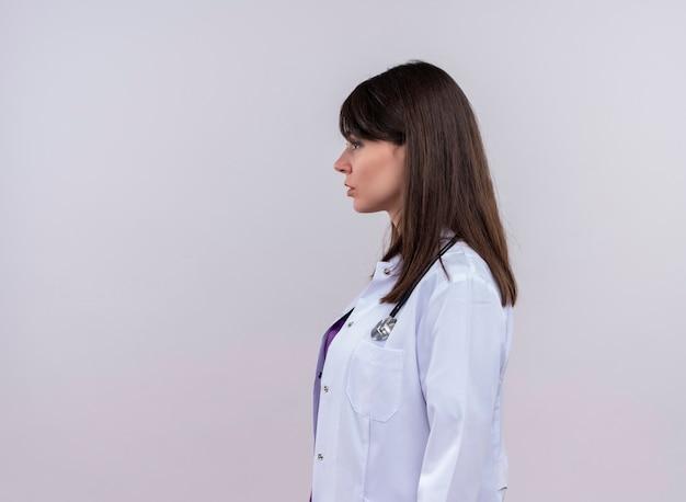 La giovane dottoressa in abito medico con lo stetoscopio si leva in piedi lateralmente sulla parete bianca isolata