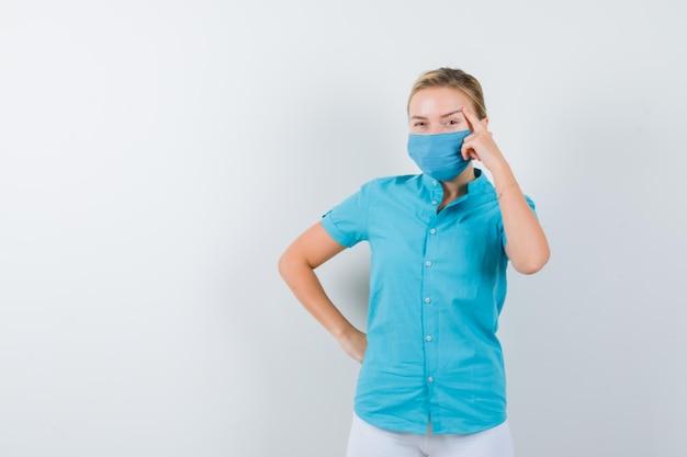 Giovane dottoressa in uniforme medica, maschera in piedi in posa pensante