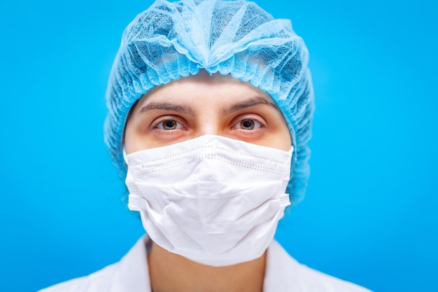 Young female doctor in medicine mask, hair cap and white gown portaiture on a blue background closeup shot.