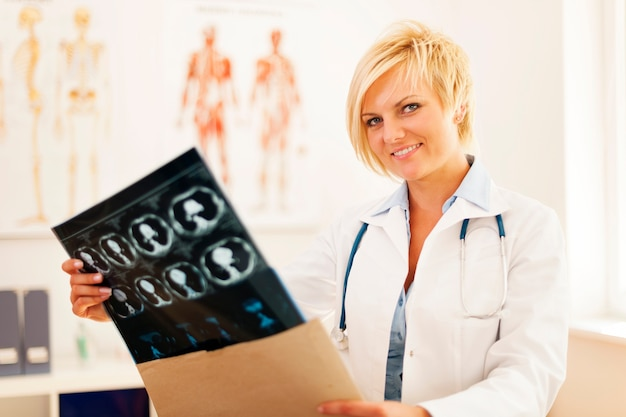 Young female doctor opening envelope with brain tomography result