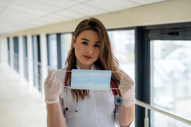 젊은 여성 의사 또는 간호사가 코로나 바이러스 covid-19로부터 보호하기 위해 마스크를 쓰고