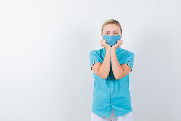 Молодая женщина-врач кладет лицо на руки в медицинской форме