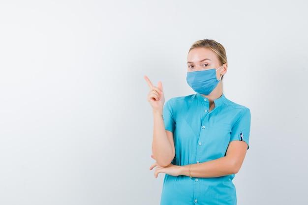 孤立した制服で左上隅を指す若い女性医師