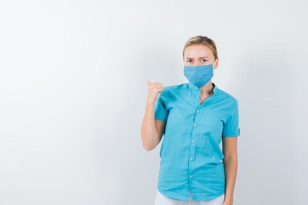 Giovane dottoressa che punta indietro con il pollice in uniforme medica