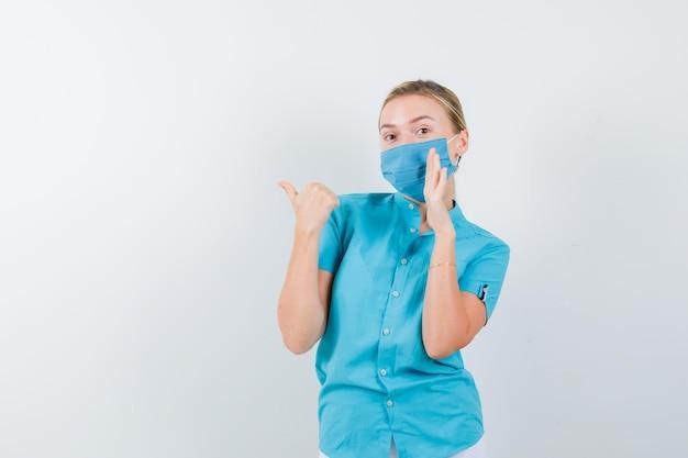 고립 된 것을 말하는 동안 왼쪽을 가리키는 젊은 여성 의사