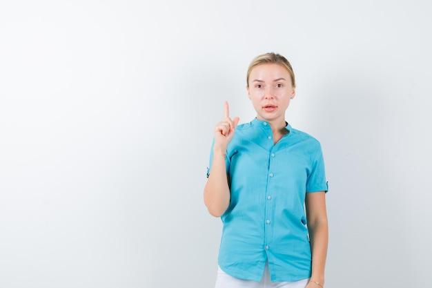 Giovane dottoressa che punta in alto in uniforme medica, maschera e sembra perplessa