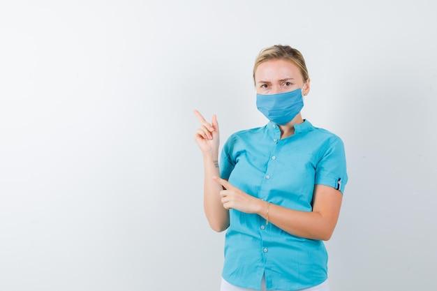 Giovane dottoressa che punta all'angolo in alto a sinistra in uniforme isolata