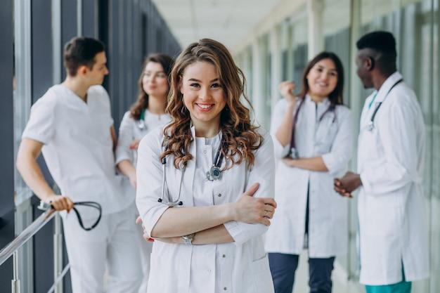 병원 복도에서 포즈를 취하는 젊은 여성 의사