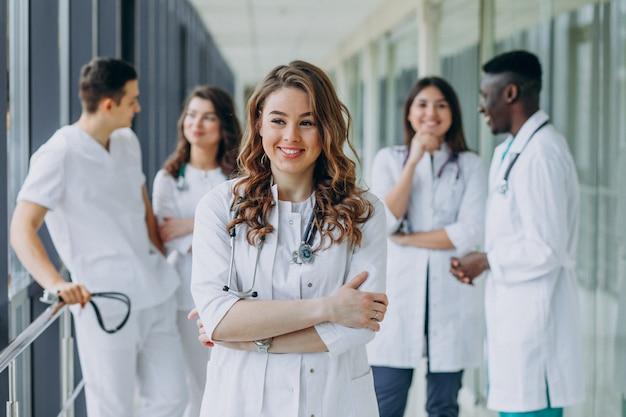 Молодая женщина-врач позирует в коридоре больницы